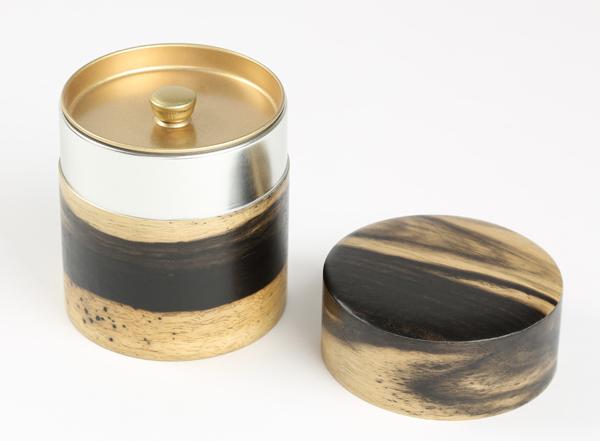 黒柿を薄くスライスしスチール缶に張り付けた茶筒になります。黒柿特有の杢目の美しさをお楽しみ下さいませ。